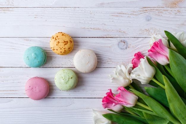 Разноцветные миндальное печенье и тюльпаны на белом фоне. копировать пространство