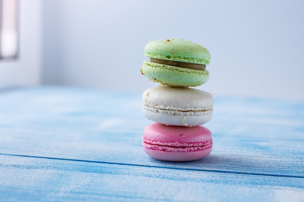 Multicolored macaroons on blue background. copy space