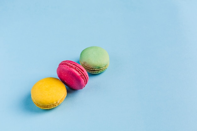 Multicolored macaroons on a blue copyspace, top view, flatley with copyspace