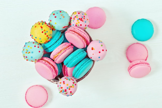 Multicolored macaroons and cake pops close up