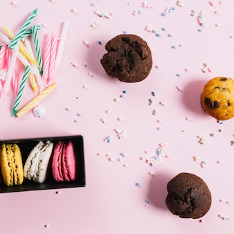 Multicolored macaroons; candles; sweet muffins; pastel sprinkles on pink background