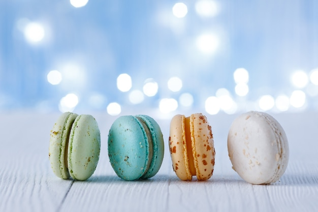 Разноцветные миндальное печенье на фоне лампочек. место для текста