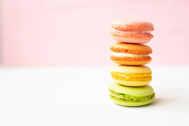 Multicolored macaroons on pink background.