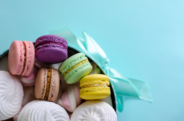 Multicolored macaroons in a turquoise box with a space for text on pastel blue