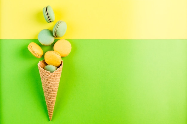 Multicolored macaroons in a waffle cone on a green and yellow copyspace, top view, flatley with copyspace