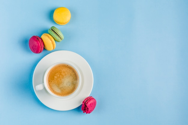 Multicolored macaroons with a white cup of coffee on a blue copyspace, top view, flat lay with copyspace