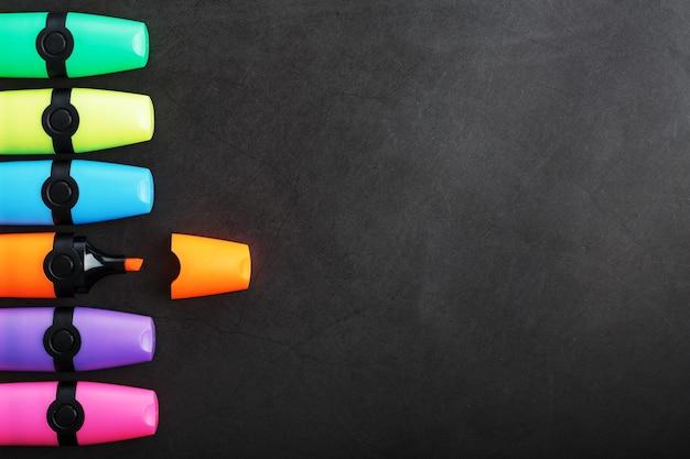 Разноцветные маркеры подряд на черном фоне вид сверху