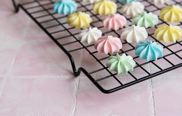 Multicolored meringue on a baking rack on a pink tile background