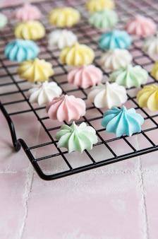 Разноцветные безе на решетке для выпечки на фоне розовой плитки