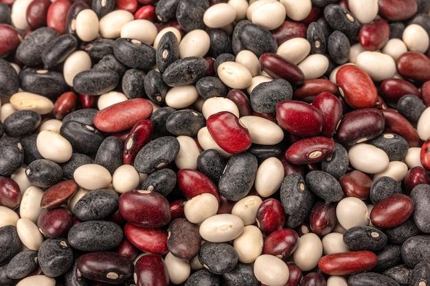 여러 가지 빛깔 된 믹스 콩 배경입니다. 강낭콩을 흰색, 빨간색, 검은 색의 세 가지 색상으로 쌓습니다. 세 가지 색상의 콩 나무 국자 숟가락