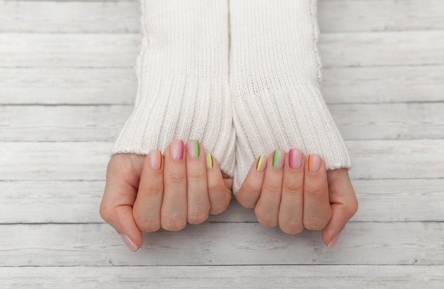 Multicolored modern manicure, nail design, summer mood, hands in a white sweater top view