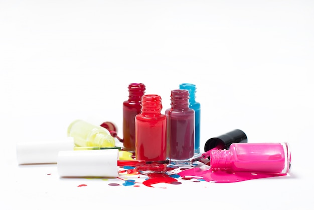 Multicolored nail polishes flowing on a white background