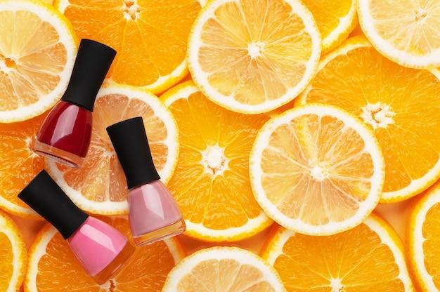 Разноцветные лаки для ногтей на вид сверху фоне цитрусовых. инструменты для профессионального маникюра и педикюра розовые и красные на апельсинах и лимонах. летняя концепция, женская красота.