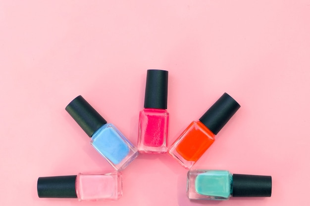 Multicolored nail polishes on a pink background. manicure concept