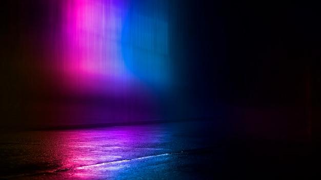 水たまりと水の抽象的な夜の背景にネオンの光の暗い街の通りの反射に色とりどりのネオンライト