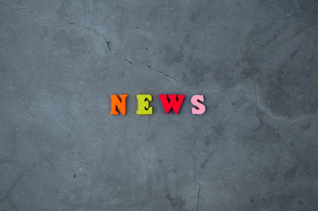 The multicolored news word is made of wooden letters on a grey plastered wall.