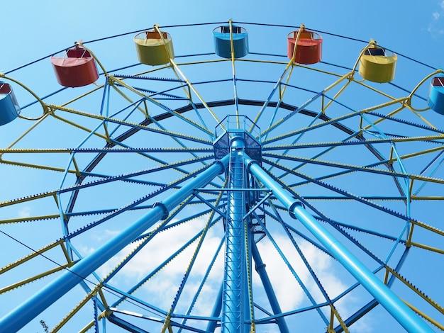 Разноцветные открытые каюты на колесе обозрения крупным планом