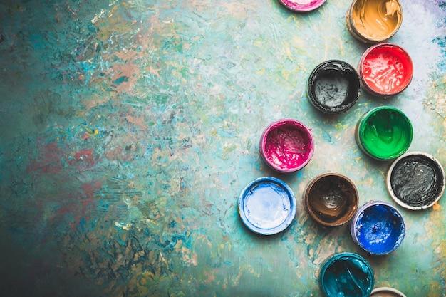 나무 배경에 여러 가지 빛깔된 페인트 캔