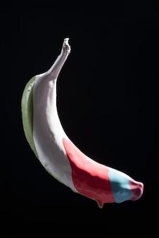 바나나 줄무늬에 여러 가지 빛깔의 페인트, 검은 배경에 여러 가지 빛깔의 바나나가 공중에 떠 있습니다.