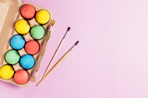 Разноцветные расписные пасхальные яйца в деревянном подносе с кистями на розовом фоне