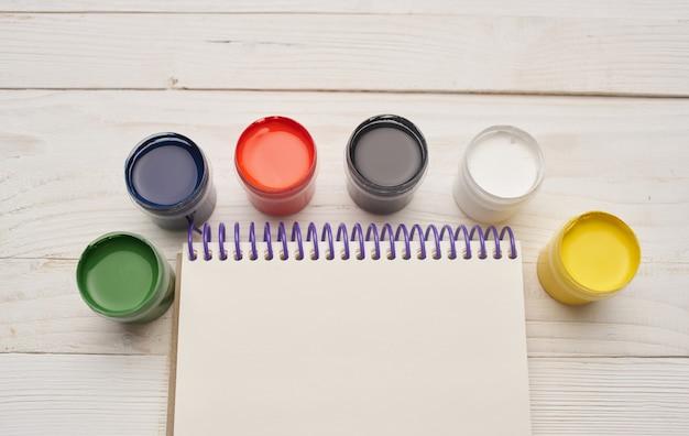Разноцветные краски и блокноты на деревянном столе рисунок фоновое изображение макет плакат