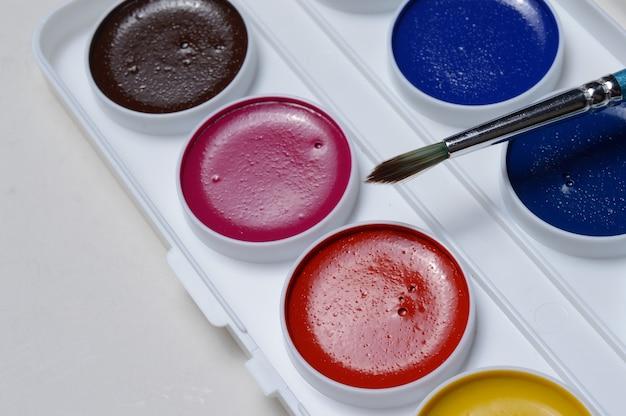 パレットとブラシで描くための色とりどりの絵の具。閉じる。
