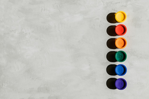 Multicolored paints jars and on a gray concrete