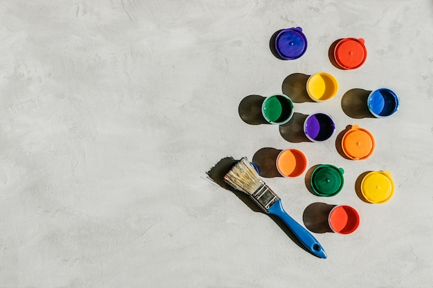Multicolored paints in round jars and brush on a gray concrete