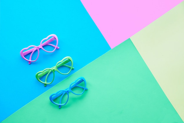 Multicolored paper background in pastel colors, flat lay, top view on three pairs of heart shaped glasses or sunglasses