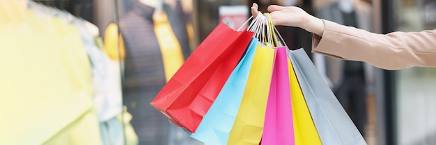 Multicolored paper bags on female hands on background of shopping mall
