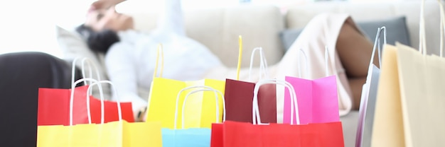 Multicolored paper bags from store stand on floor and the woman lies on couch