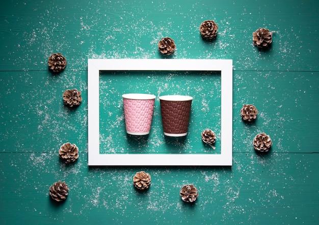 Разноцветные бумажные кофейные чашки лежат в белой рамке на бирюзовом деревянном фоне, усыпанном