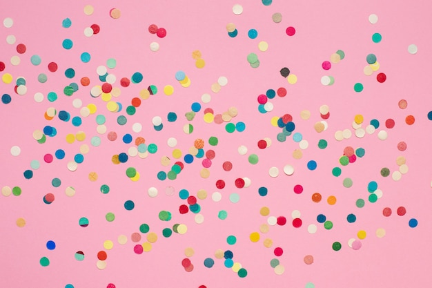Разноцветные бумажные конфетти на розовой изолированной поверхности