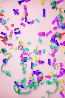 Multicolored paper confetti on a pink background