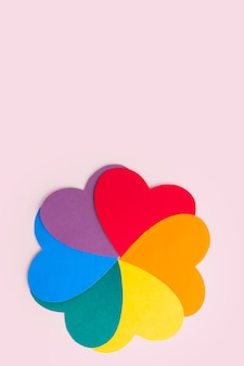 Multicolored paper hearts forming a flower shape with rainbow petals on a pink surface, vertical frame, copy space. lgbt concept