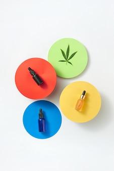 ライトグレーのテーブル、コピースペースに天然医療大麻エッセンシャルcbdオイルのボトルが入った色とりどりの紙の丸いカード。医療目的での大麻の使用。上面図。