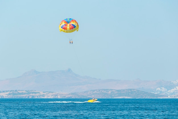 ボートで引っ張られる色とりどりのパラセールウィング。海の夏のレクリエーション-トルコ、ボドルム。