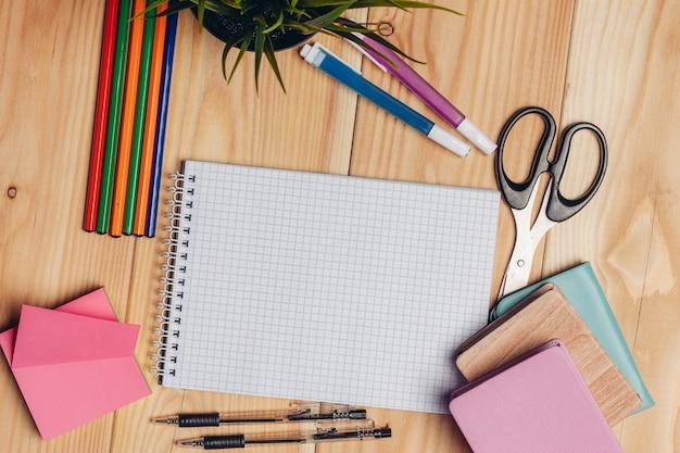 Разноцветные карандаши и маркеры, ножницы, бумага для творчества, настольная школа. фото высокого качества
