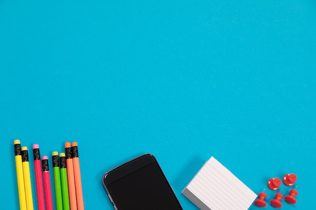 Multicolored pencils, black mobile phone, a pile of white scratch paper and a group of red pushpins are half visible lying on a pale-blue surface isolated Premium Photo