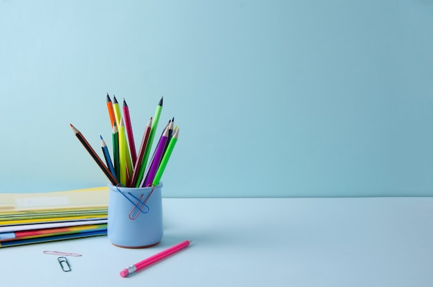 青い背景に青いスタンドに色とりどりの鉛筆。