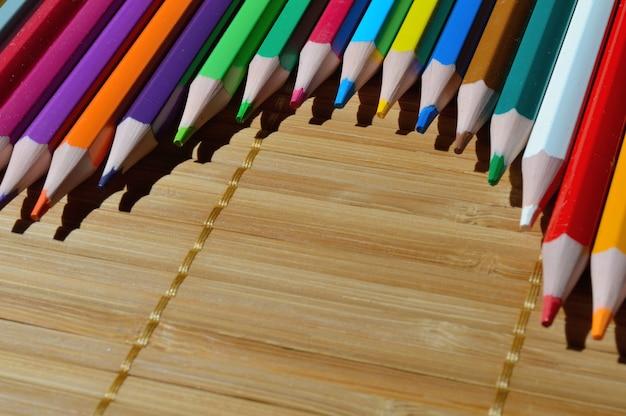 わらの背景に弧を描いて配置された色とりどりの鉛筆。