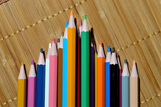 Multicolored pencils lined with a wedge on a straw background.