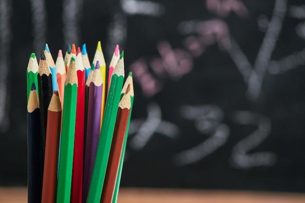 Multicolored pencils over school board, school, university, college