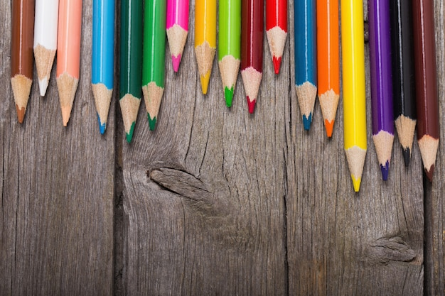 Multicolored pencils on the wooden background