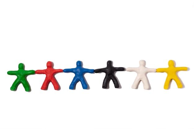Разноцветные люди из пластилина, держась за руки, лежат на белом фоне