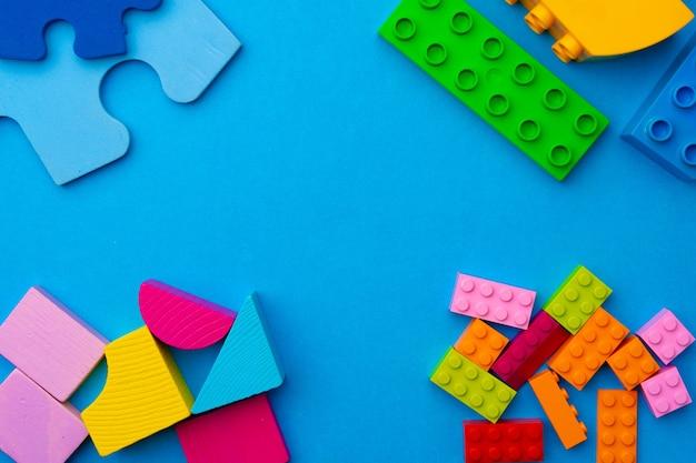 파란색 표면에 장난감 생성자의 여러 조각