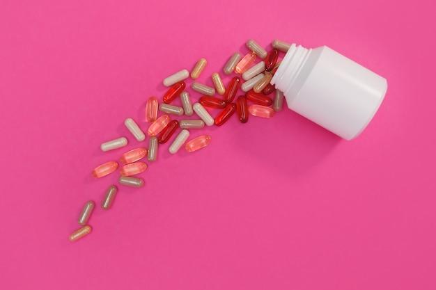 분홍색 배경에 여러 가지 빛깔의 알약과 캡슐
