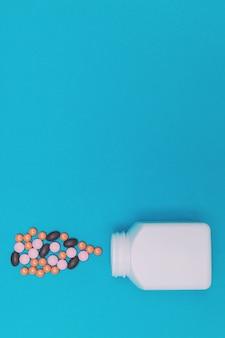 파란색 배경에 항아리에서 떨어지는 여러 가지 빛깔의 알약