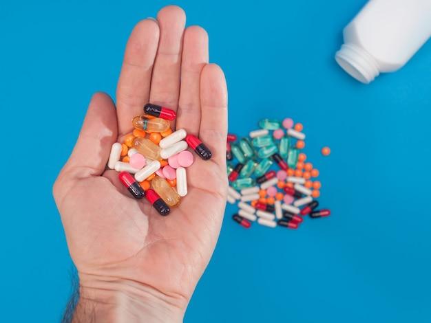파란색 배경에 손에 여러 가지 빛깔된 약