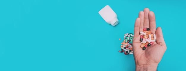 파란색 파노라마 배경에 손에 여러 가지 빛깔의 알약